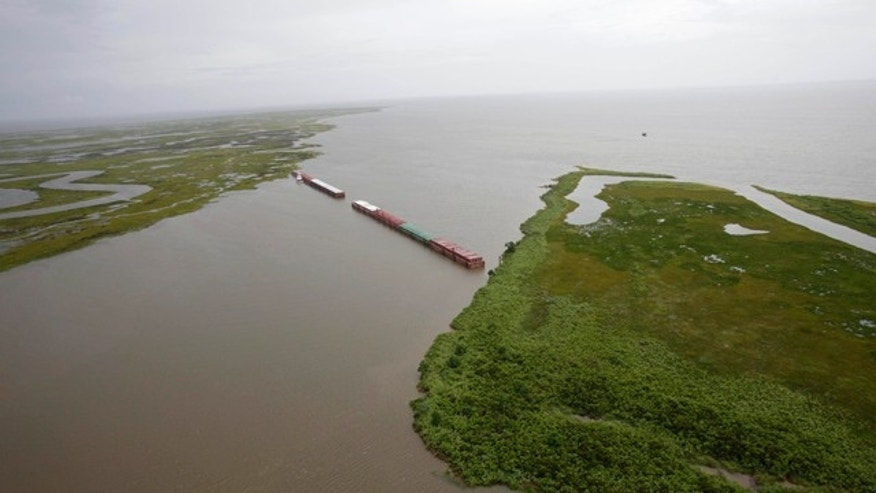 July 6: Barges lined up to block oil are seen from the air in Chef Menteur Pass, which connects the Gulf of Mexico and Lake Borgne to Lake Pontchartrain, in New Orleans, La.