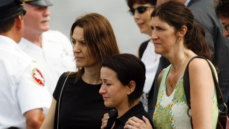 July 8: Two Hungarian teachers, who survived a duck boat crash on Wednesday, are consoled by a U.S. woman, who served as a host for a Hungarian student group, as they view the site where two of their students went missing on the Delaware River in Philadelphia. (AP)