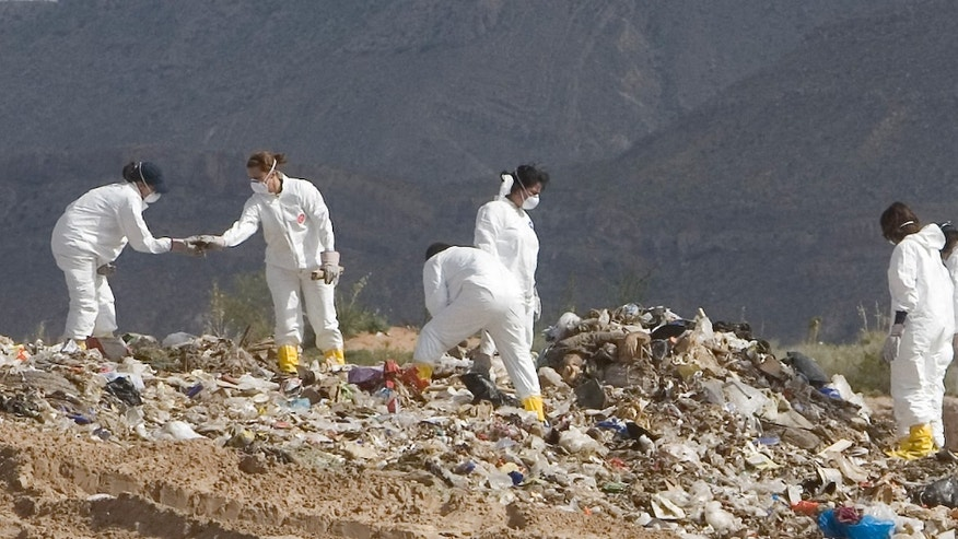 The crime scene unit with the El Paso County Sheriff's Office works to recover the body of Carlos Roberto Medina-Bailon at a landfill in New Mexico