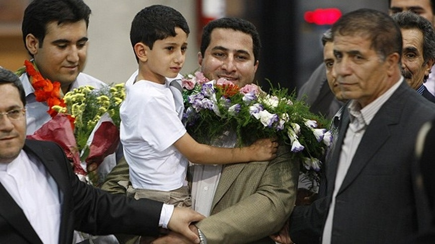 July 15: Shahram Amiri holds his 7-year-old son as he returns to a hero's welcome near Tehran, Iran.