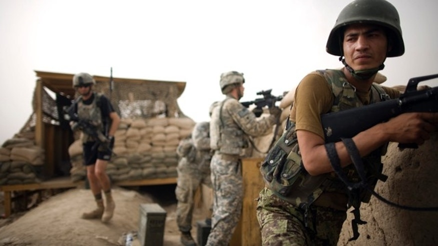 July 23, 2010: Afghan National Army soldiers and U.S. Army soldiers from the 1-320th Alpha Battery, 2nd Brigade of the 101st Airborne Division stand guard after an insurgent attack at COP Nolen, in the volatile Arghandab Valley, Kandahar, Afghanistan.