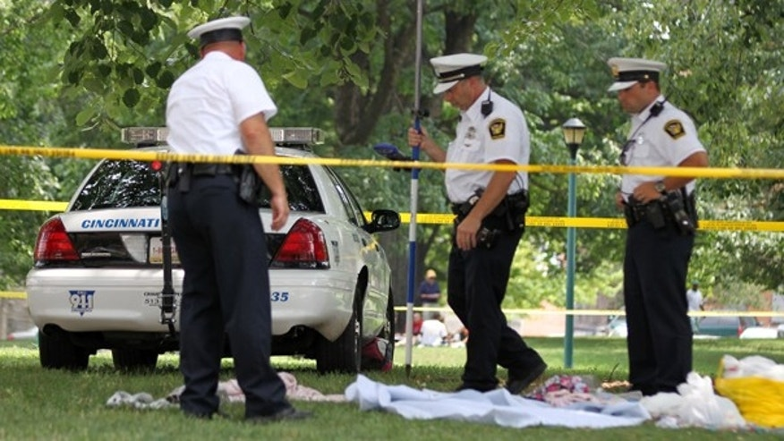 July 27: Cincinnati Police officers on the scene where a women, presumed to be homeless, was sleeping on the ground when she was hit by a Cincinnati Police park unit vehicle that was trying to cut across Washington Park. (AP)
