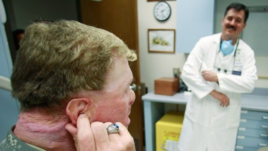 June 23: Master Sgt. Todd Nelson, left, visits with Dr. Joe Villalobos, right, during a visit to makes adjustments to a prosthetics ear at Wilford Hall Medical Center in San Antonio. Nelson was injured in 2007 by an explosion while serving in Afghanistan. (AP)
