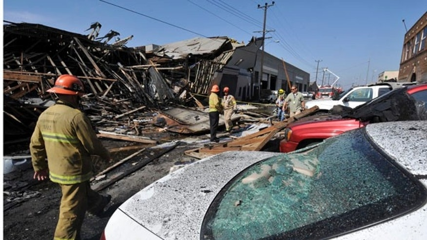 July 30: Los Angeles city fire fighters survey damage after a suspected natural gas explosion at a welding shop collapsed part of the building and killed two people in Los Angeles.