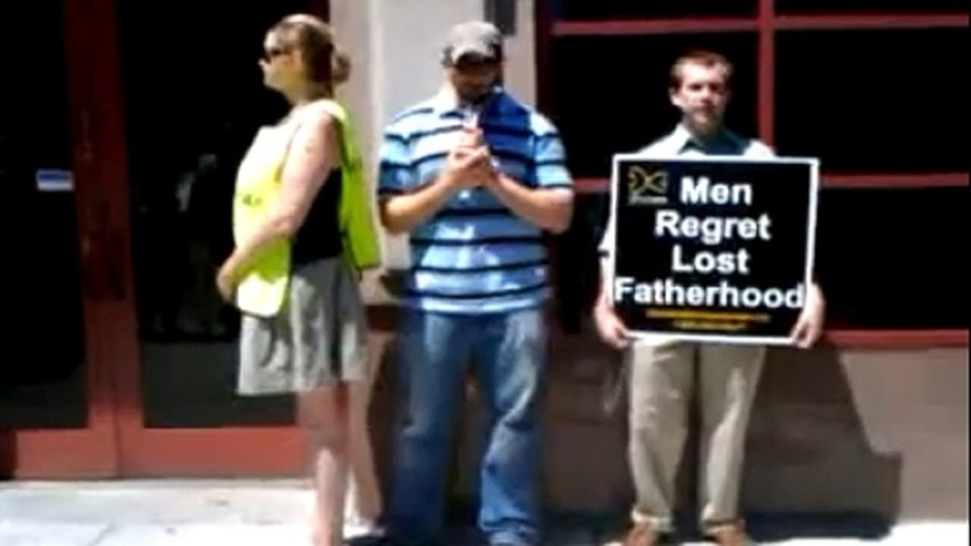Complaining witness, left, stands next to Joe Holland, middle, as he prays the rosary outside Planned Parenthood's Near North Center in Chicago.
