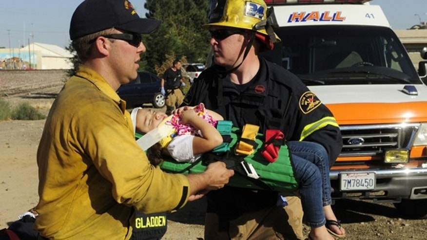 Aug. 6: Emergency personnel carry an injured child from the collision scene in Shafter, Calif. An Amtrak train collided with a semi-truck when the truck attempted to outrun the train at a railroad crossing.