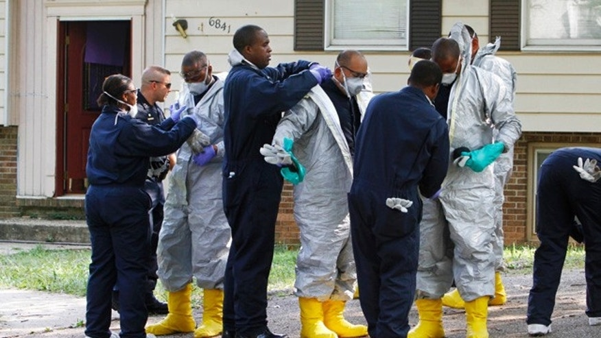 Aug. 6: Prince George's County, Md. police academy recruits wear protective gear to search for evidence on the property where four bodies were found in a garage in Riverdale, Md.