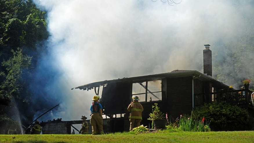 Firefighters work at the scene where authorities say a twin-engine plane crashed into a house in  Bell Township, Pa.,