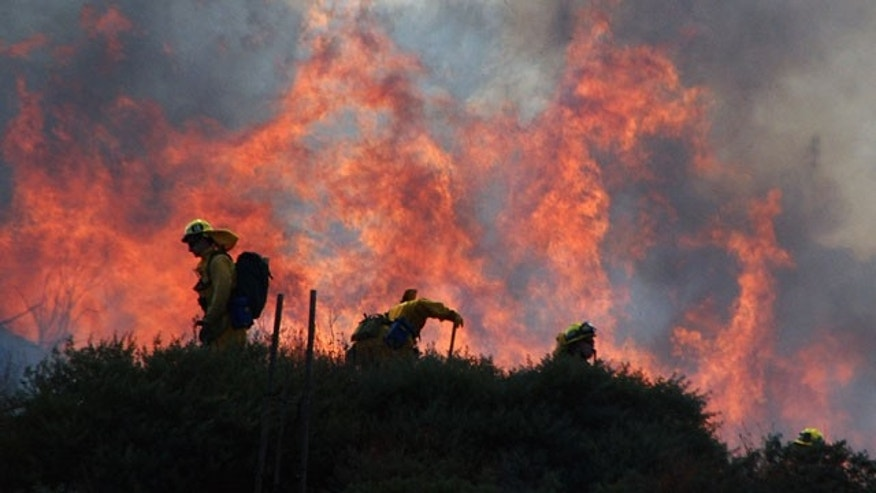 Aug. 8: Los Angeles County firefighters work to cut a firebreak above an exclusive housing tract as flames shoot up the hillside they are working on.