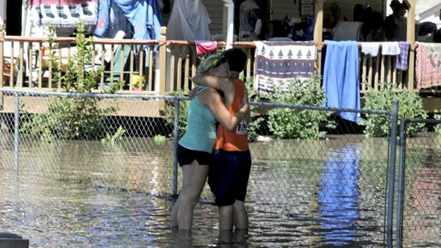 Aug. 11: Residents embrace, as floodwater from the South Skunk River flood neighborhoods in Colfax, Iowa.