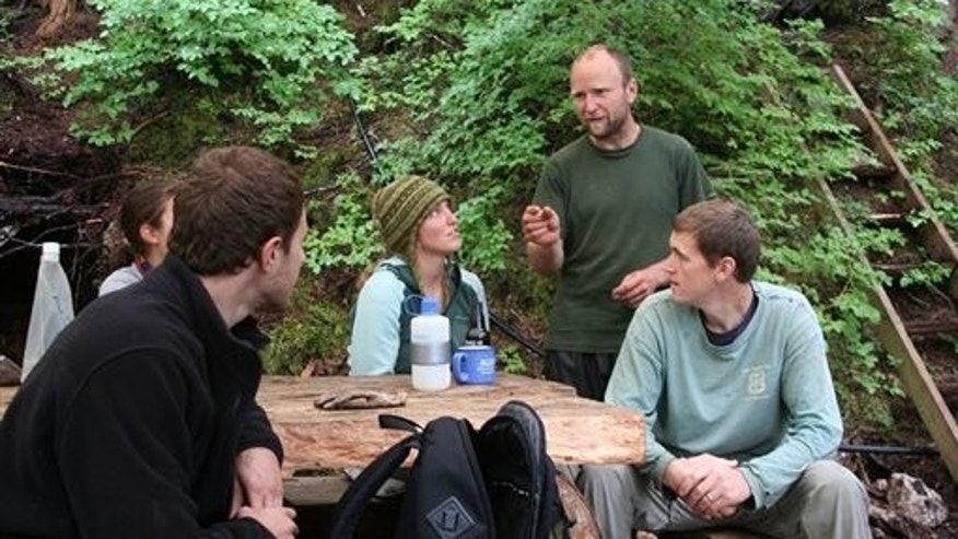 August 8: Rick Bellagh stands while talking to World Wide Opportunities on Organic Farms volunteers , Sarah Douglass, from left, Robert Mulloy, Gracy Carpenter and Scott Carpenter , in Shelter Island in Juneau, Alaska. Bellagh, who moved to Juneau two years ago, pared down his life, sold his car and started spending half the year out on his seven-acre plot on Shelter Island. He is trying to create an organic community. (AP)