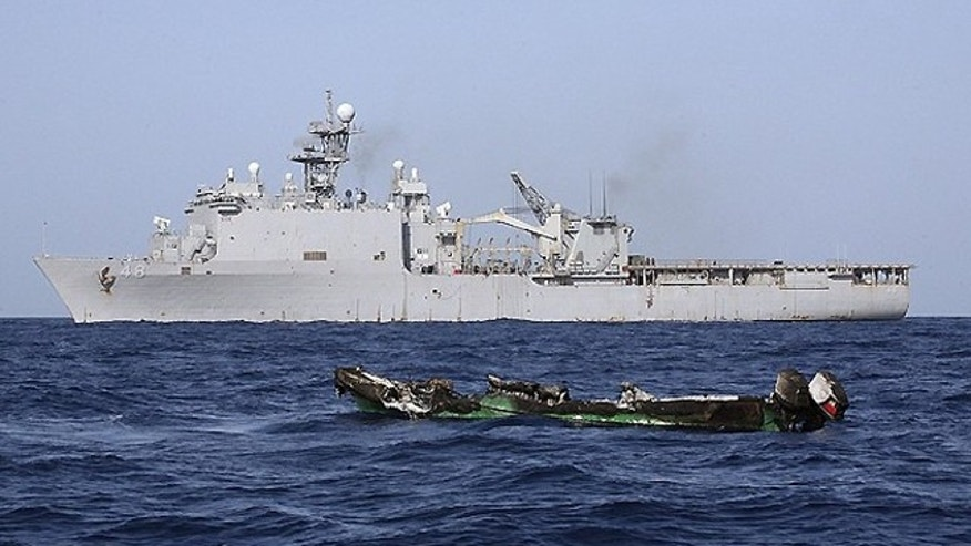 April 10, 2010: The burned out hull of a suspected pirate skiff drifts in the Gulf of Aden in front of the USS Ashland. (Reuters)