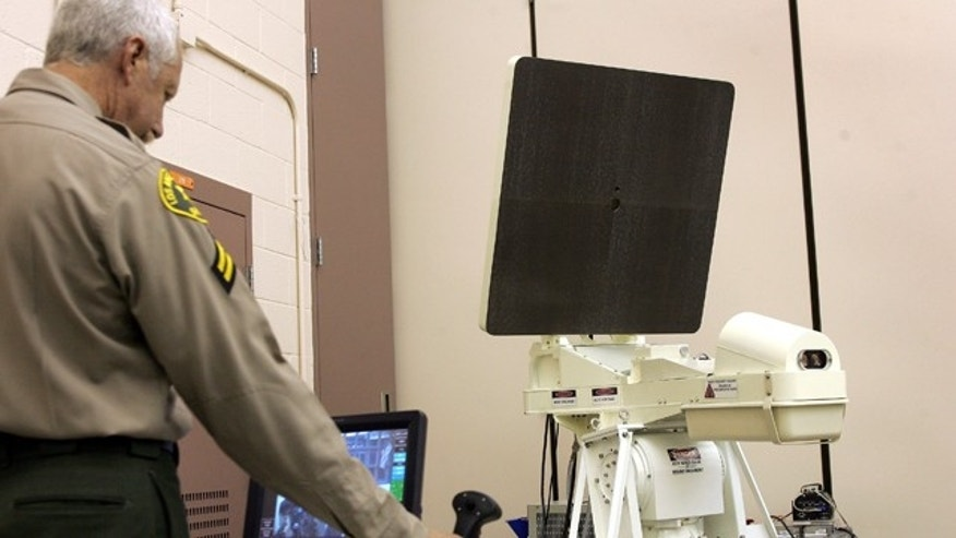 Aug. 20: Los Angeles County Sheriff's Department Senior Deputy David Judge aims the Assault Intervention Device (AID) with a toggle during a demonstration at the Pitchess Detention Center's North County Correction Facility in Santa Clarita, Calif.