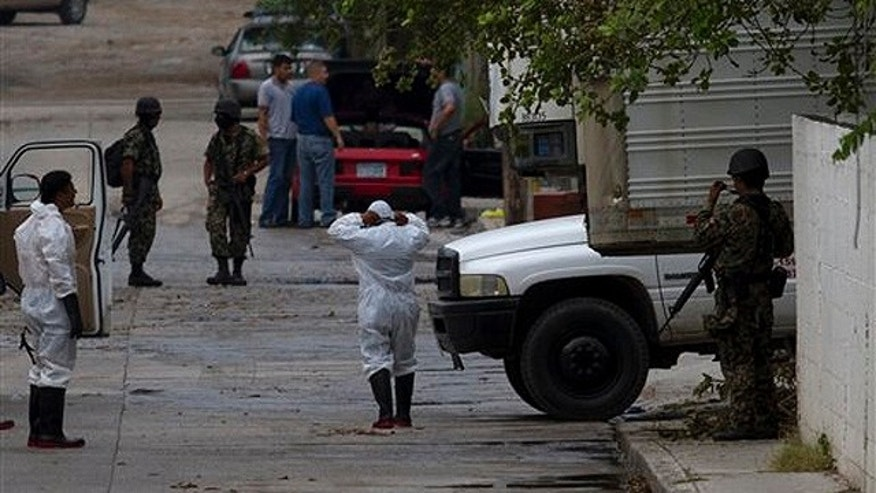 Aug. 23: Mortuary worker wearing protective suits and Mexican marines are seen outside a funeral home where the bodies of 72 men and women that were allegedly killed by the Zetas drug gang are kept in San Fernando, just 100 miles from the Mexican border with the U.S. near the city of Matamoros, Mexico.