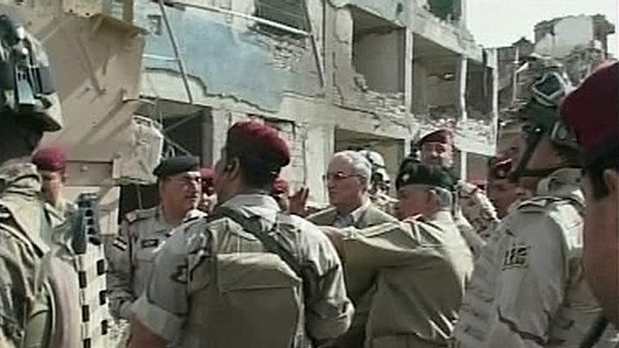 In this image made from television, Iraqi Defense Minister Abdul-Qadir al-Ubaidi , center, inspects the site of a suicide attack accompanied by soldiers at a military headquarters in Baghdad, Sunday, Sept. 5, 2010. Suicide bombers hit a Baghdad military headquarters on Sunday and killed dozens of people, two weeks after an attack on the same site pointed to the failure of Iraqi forces to plug even the most obvious holes in their security. (AP Photo/APTN)