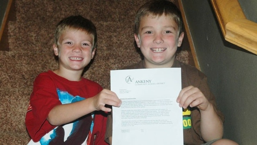 Benny, 5, and Nate, 7, hold a letter from their school district containing the four-digit PIN numbers they'll need to memorize in order to have lunch at school.