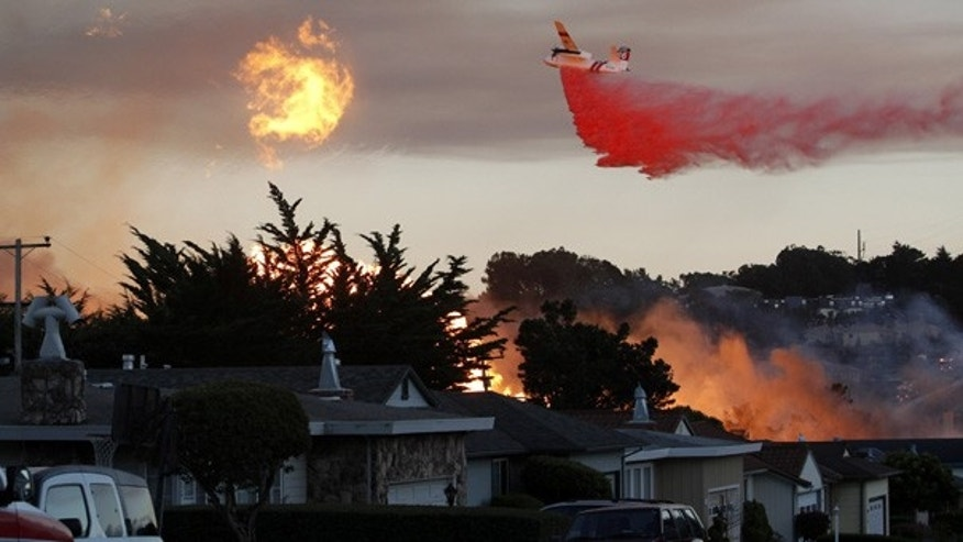 FILE: In this Sept. 9, 2010, photo, an air tanker drops fire retardant on a San Bruno, Calif., neighborhood as a massive fire destroys homes.