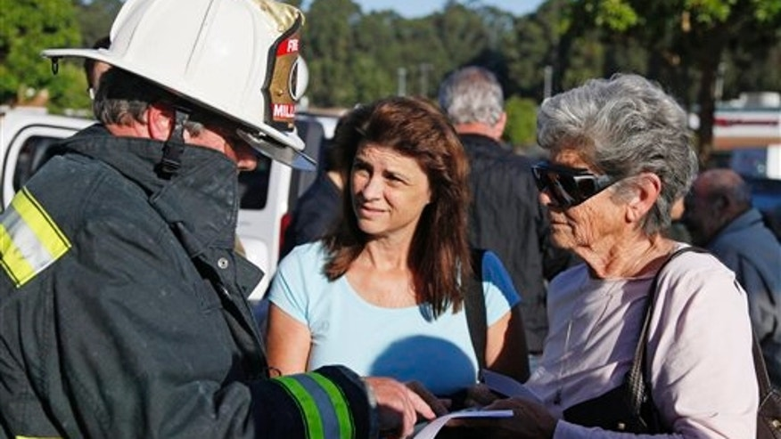 Millbrae, Calif., fire chief Dennis Haage, left, talks with San Bruno, Calif., residents Toni Vaccari, right, and her daughter, Debbie Shea, about returning to their homes near last night's gas explosion following a news conference, Friday, Sept. 10, 2010, at a shopping center in San Bruno. Fire crews sprayed water on smoldering homes Friday morning after a massive explosion apparently triggered by a broken gas line sent flames roaring through a neighborhood near San Francisco, killing at least six people and injuring dozens, officials said. (AP Photo/Eric Risberg)