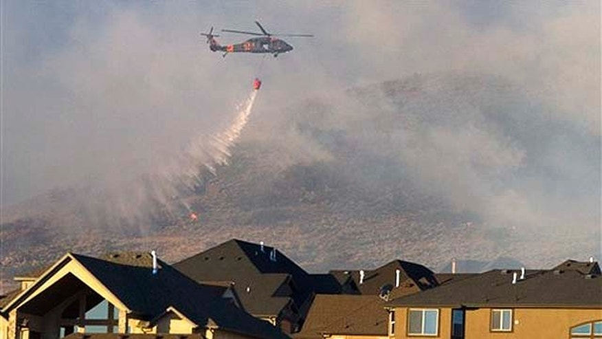 Sept. 20:  A helicopter is used to drop water on the wildfire that burns in the foothills of Herriman, Utah. A wind-stoked wildfire sparked at a firing range during a National Guard training session blazed across thousands of acres Monday as crews rushed to keep it from burning more than four homes that were destroyed overnight. The fire moved back on itself Monday as the Utah National Guard acknowledged it wasn't the first time that live-fire exercises had sparked a fire at Camp Williams, a sprawling compound 30 miles south of Salt Lake City.
