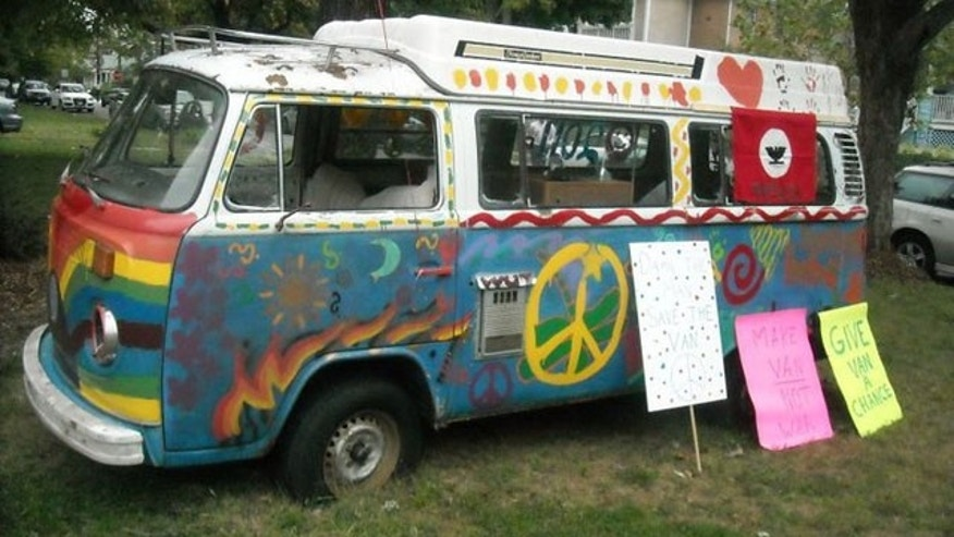 "A view of the ""Peace-Mobile"" displaying its graffiti and rally picket-signs."