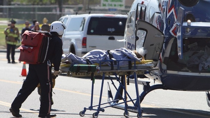 Oct. 8: An injured student is wheeled to a helicopter after a lone gunman came on to the campus of nearby Kelly Elementary School.