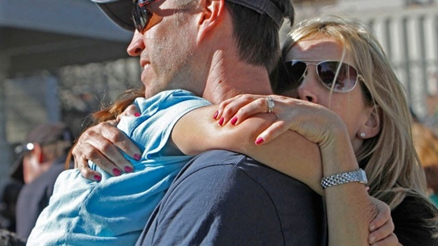 A mother and father hug their daughter at Kelly Elementary School where a gunman wounded two children after opening fire Friday, Oct. 8, 2010, in Carlsbad, Calif.