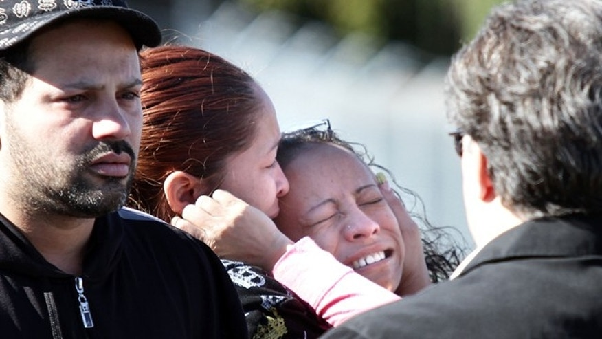 A family member of a ParkOhio Products Inc. employee who is believed to be a victim of a homicide is consoled as she cries in front of the building Friday, Oct. 22, 2010, in Cleveland. Police say two people were fatally shot at the manufacturing plant, and a suspect is in custody. (AP Photo/The Plain Dealer, Joshua Gunter) MANDATORY CREDIT