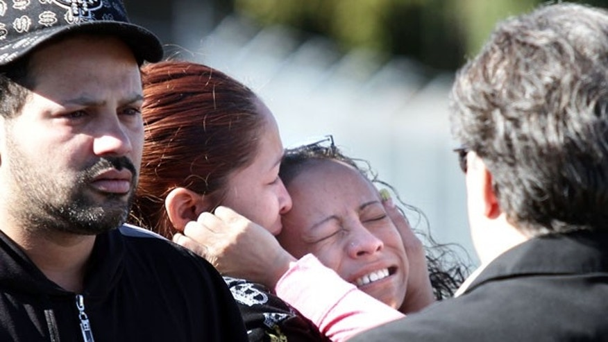 Oct. 22: A family member of a ParkOhio Products Inc. employee who was fatally shot at the manufacturing plant is consoled as she cries in front of the building in Cleveland, Ohio. Pedro Rodriguez is believed to have killed plant worker Graciela Morales outside, then used her employee ID card to get inside the building and fatally shoot worker Eduardo Pupo.