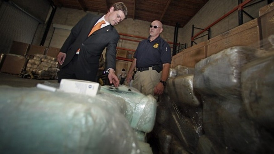 Nov. 3:  Director of Immigration and Customs Enforcement John Morton, left, inspects a bundle of marijuana with a Homeland Security agent at a warehouse near the U.S.-Mexico border.