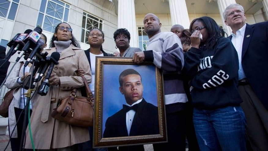 Nov. 8: Monique Revaida, far left, mother of Bobby Tillman, 18, in the portrait being held, stands with loved ones in front of the Douglas County Courthouse after a hearing regarding the four men charged in her son's death at an overnight brawl in Douglasville, Ga.