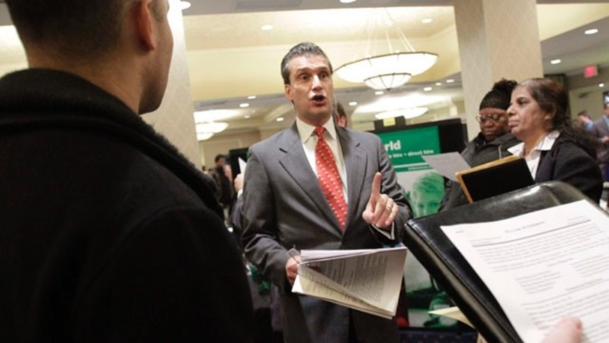 Nov. 9: A recruiter, center, speaks to job applicants during a job fair at the The Radisson Martinique hotel in New York.