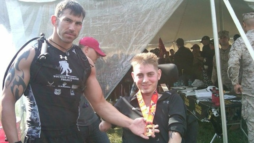 Oct. 31: Marine Sgt. Jeremy Soles, left, presents Cpl. John Peck, right, with the Marine Corps Marathon Finisher medal after Soles ran the 26.2-mile marathon in a gas mask (FoxNews.com).