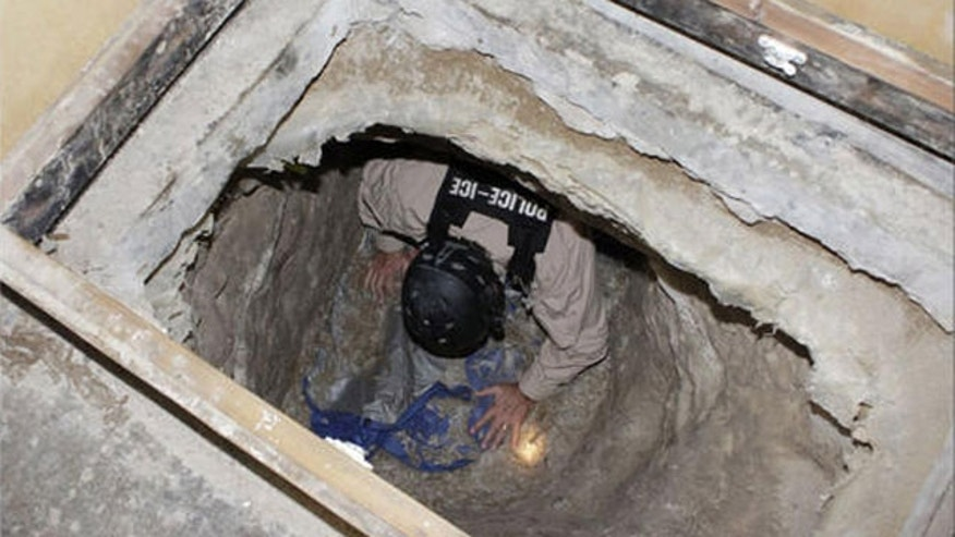 A federal agent crawls through a 600-yard tunnel found in a warehouse on Nov. 3, along the border between the US and Mexico, San Diego.