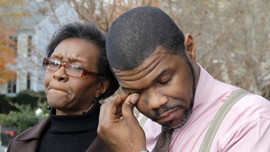 Nov. 23: Anthony Tisdale, right, father of Delvonte Tisdale, wipes his face during a news conference in front of his home in Charlotte, N.C. Investigators say they are now looking into the possibility that the Charlotte teenager, whose mutilated body was found on a suburban Boson street, may have fallen from a plane.