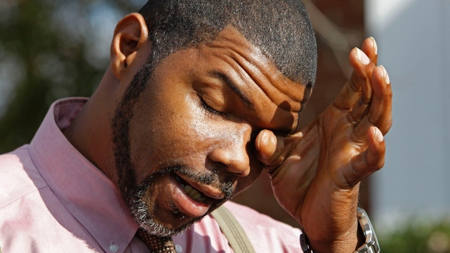 Nov. 23: Anthony Tisdale, right, father of Delvonte Tisdale, wipes his face during a news conference in front of his home in Charlotte, N.C.