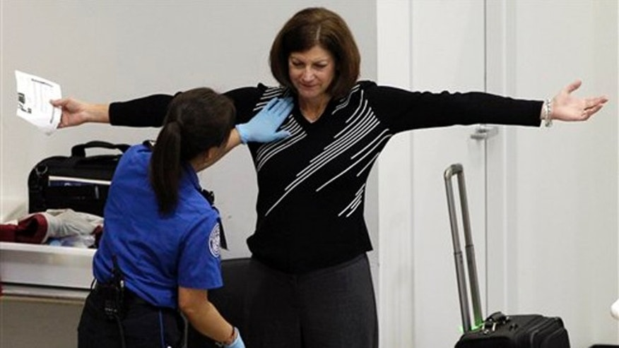 A woman undergoes a pat-down during TSA security screening, Friday, Nov. 19, 2010, at Seattle-Tacoma International Airport in Seattle.