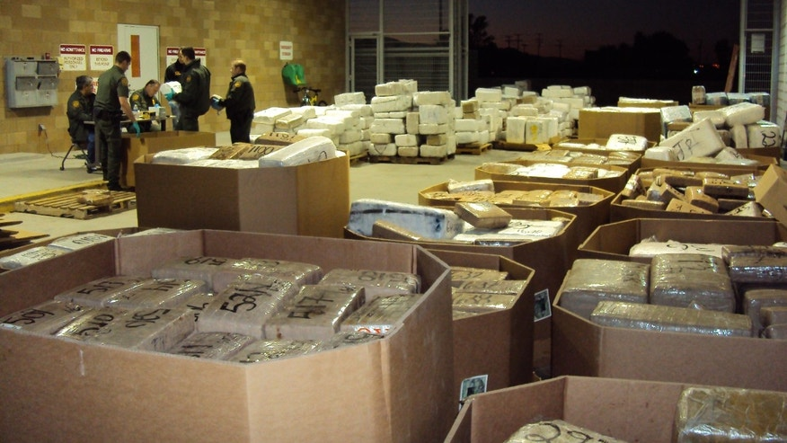 In this Nov. 25, 2010 photo released by U.S. Immigration and Customs Enforcement (ICE), packages of seized marijuana are examined by officials in Murrieta, Calif., after a cross-border tunnel between Tijuana, Mexico and San Diego was discovered.