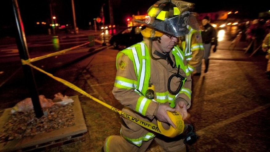 Nov. 29, 2010: A firefighter sets up a tape line in a parking lot a few blocks from Marinette High School after a student armed with a handgun burst into a classroom at the northern Wisconsin school.