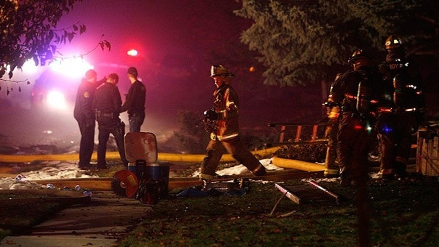 Dec. 5: Firefighters and police comb through plane crash wreckage in front of a home in Roy, Utah.