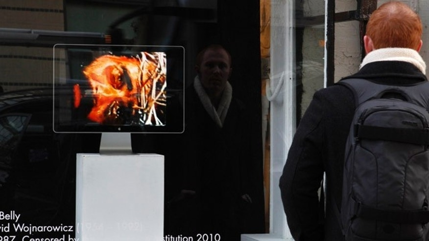 "Dec. 2: A man watches the video, ""A Fire in My Belly"" outside the Transformer Gallery in Washington."