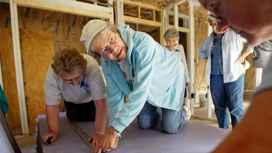 Nov. 19: Sister Joyce Richter, center, discusses a measurement on a sheet of drywall with fellow Catholic nuns while volunteering to rebuild a Hurricane Katrina-damaged house in New Orleans.
