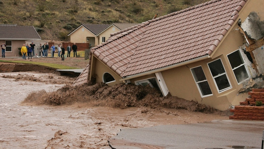 Dec. 21: A house in the Beaver Dam Resort area falls into the Beaver Dam Wash in Beaver Dam, Ariz. Heavy rains caused the wash to swell over its banks destroying roads and so far five homes along its path.