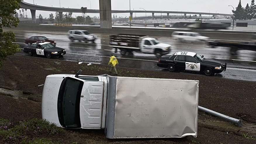 Dec. 29: A truck lands on its side after the driver lost control while driving too fast in the rain, and flipped over on the right shoulder of the northbound 57 in Anaheim, Calif.