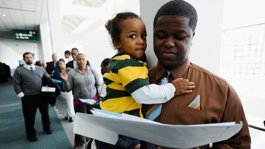 Dec. 1: Antoine Young and his son wait with fellow job seekers to enter the Choice Career Fair in Los Angeles.