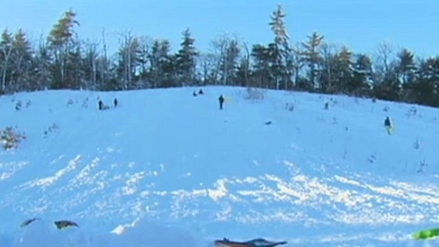 A Massachusetts town has police patrolling to prevent children from sledding down a slope school officials deem dangerous.