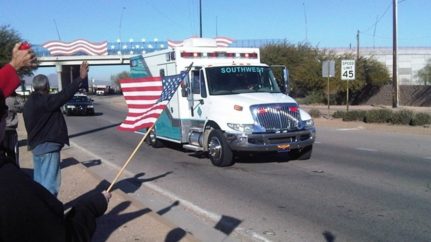 Jan. 21: An ambulance carries Rep. Gabrielle Giffords along a route lined with well-wishers holding flags Friday. (Fox News)