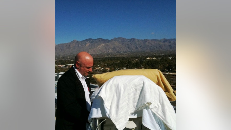 Jan. 20, 2011: Navy Capt. Mark Kelly, husband of Congressman Giffords, covered with a blanket, stands with her on an outdoor deck at University Medical Center in Tucson looking north at the Catalina Mountains.