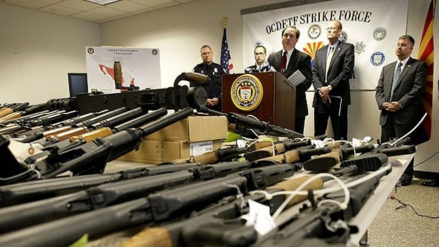 Jan. 25: United States Attorney for Arizona Dennis Burke speaks behind a cache of seized weapons in Phoenix.