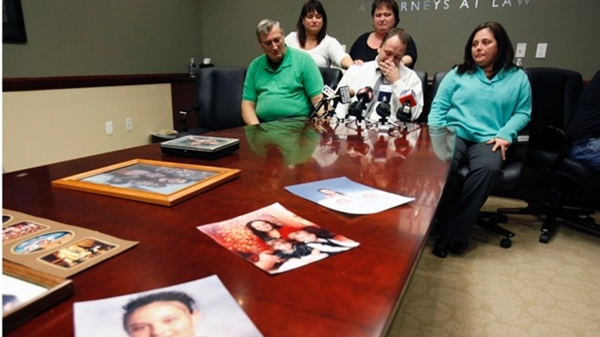 In this Jan. 27, 2011 file photo, family members Mark Szpila, front center, Elmer Barthelemy, front left, Lynn Barthelemy, front right, Dawn Barthelemy, back left, and Susan Szpila, back center, speak about Melissa Barthelemy, pictured in family photographs on the desk, during a news conference in Amherst, N.Y. Barthelemy was one of four women whose bodies were dumped along a desolate beachfront strip on Long Island. Authorities say all were prostitutes who booked their clients online and were probably slain by a serial killer.