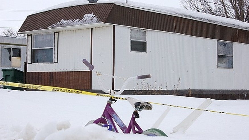 Jan. 29: Crime-scene tape and a snow-buried bicycle are seen in front of a trailer home in Minot, N.D., where the bodies of a mother, her boyfriend and her son were found a day earlier. A daughter was found dead in an apartment home in a related incident.